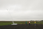 CHAD PILSTER •Hays Daily News<br /> <br /> (left to right) Kwinter Hartsthorn, 17, Bison, launches his rocket as Dennis Elder, Bison, the coordinator of the event, Phillip Scheuerman, Bison, and Xander Palmberg, 9, watch on Saturday, August 3, 2013, during the 4-H and Open Class Rocket launch as part of the Rush County Fair at the Rush County Airport in La Crosse, Kansas.