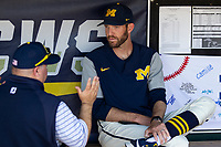 Michigan Wolverines pitching coach Chris Fetter (41) in the dugout before taking on the Vanderbilt Commodores during Game 1 of the NCAA College World Series Finals on June 24, 2019 at TD Ameritrade Park in Omaha, Nebraska. Michigan defeated Vanderbilt 7-4. (Andrew Woolley/Four Seam Images)