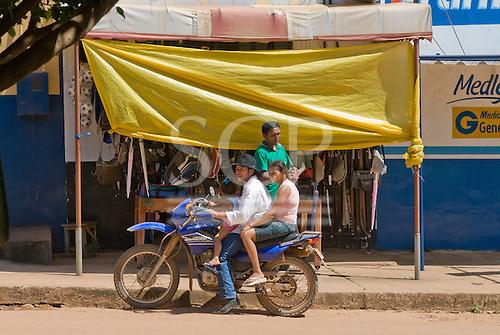 Pará State, Brazil. São Félix do Xingu. Family transport; three on a motorbike.