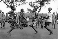 Uganda. West Nile. Adjumani. Ogujebe is distant 15 km from Adjumani. It is a transit camp for refugees from South Sudan. Three young girls and a boy are playing and jumping over the rope. West Nile sub-region (previously known as West Nile Province and West Nile District) is a region in north-western Uganda. © 1989 Didier Ruef