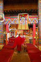 Buddhist monk walks between prayer beds in the main hall of Ramoche Temple, amid embroidered silk adorned columns with central sacred painting, or thangka, of Tsongkhapa, founder of Gelugpa Buddhism. Built in the 7th century, sister to the Jokhang Temple, Lhasa, Tibet, China.