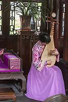 Yangzhou, Jiangsu, China.  Woman Playing a Pipa, Ho Family House and Garden.