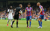 Pictured: Match referee C Pawson speaks to L-R Marvin Emnes of Swansea, Mile Jedinak and Brede Hangeland<br />