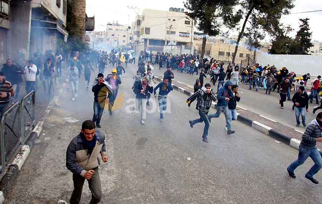 Palestinians protesters clash with Israeli soldiers during a demonstration commemorating 18 years to the Hebron massacre and calling to open Shuhada street in the West Bank city of Hebron, Friday, Feb. 24, 2012. In 1994, an American-born Jewish settler, Baruch Goldstein, entered the room in the Tomb of the Patriarchs that serves as a mosque and shot dead 29 Palestinian worshippers before survivors overwhelmed him and beat him to death. Photo by Issam Rimawi