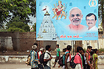 13 September, 2013, Ahmedabad, Gujarat INDIA :  Pilgrims walk past a poster of  Chief Minister of Gujarat , Narendra Modi (centre) in Ahmedabad.   Mr. Modi has been announced as the Prime Ministerial candidate for the opposition BJP party in the Indian general elections slated for 2014.   Mr.Modi has been a controversial figure since his involvement in the 2002 Gujarat riots where a train full of Hindu pilgrims was attacked by Muslims returning from a disputed temple site in Ayodhya.  In retaliation some estimate up to 2000 Muslims lost their lives in communal violence.   Mr. Modi is alleged to have condoned the violence despite being cleared of any allegations by a Special Investigation Team (SIT) appointed by the Supreme Court of India. Picture by Graham Crouch/New York Times