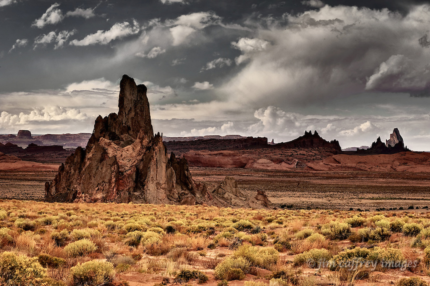 A volcanic lava neck stands in the desert east of Kayenta Arizona with more volcanic formations on the distance, all under a stormy sky.