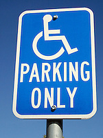 Closeup of a handicapped parking only sign mounted on a pole