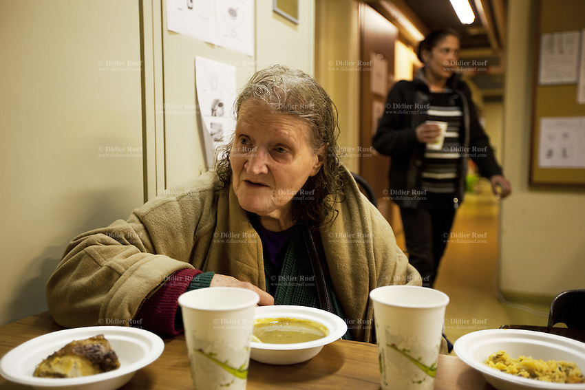 Switzerland. Geneva. Katie Clarke is a british citizen and used to be a soprano singer. She is now a homeless woman seated on a chair and eating supper in the fallout shelter Richemont. A Romani woman from Romania is also spending the night in the the shed. The bunker was constructed as civil defense measures during the Cold War and is a unit of the Civil Protection. Switzerland is unique in having enough nuclear fallout shelters to accommodate its entire population. Romani are widely known by the exonym Gypsies (or Gipsies) and also as Romany, Romanies, Romanis, Roma or Roms. 7.02.2014 © 2014 Didier Ruef