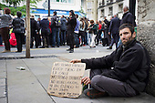 I have no family, I am thrown on the street, I have no work, no benefits.  A homeless man begs on a street corner during a religious parade in Granada, Spain.
