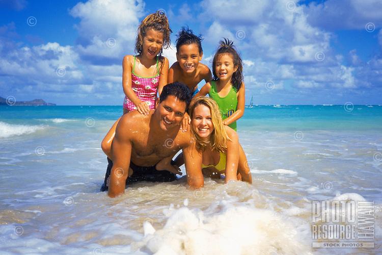 Multi-ethnic family making a pyramid at beach setting, Oahu, Hawaii