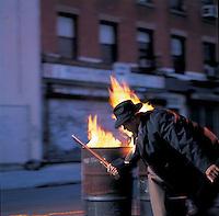 Man in suit swinging nightstick in front of fire barrels<br />