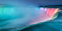 Amazing Niagara Falls horseshoe close-up, at twilight with mist, city lights, and water colored with rainbow lights, in Canada