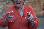 Drinking alcohol woman has a glass of wine and smokes a cigarette, she holds another for a friend  Arles France 2010s