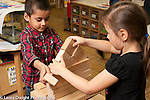 Education Preschool 4 year olds boy and girl working together to build block structure