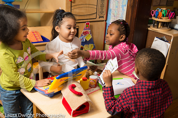 Education Preschool 3-4 year olds pretend play group of three girls and a boy playing game with turn taking and rules