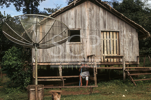 Amapa State, brazil. Caboclo woman with a bandage on her knee in front of her wooden house with a satellite dish.