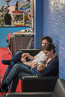 A mother breastfeeds her 5 month old son at a play centre. Her husband is sitting beside her.<br /> <br /> Hampshire, England, UK<br /> 21/03/2016<br /> <br /> © Paul Carter / wdiip.co.uk