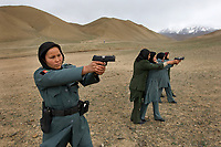 Policewomen practicing shootings at shooting range.