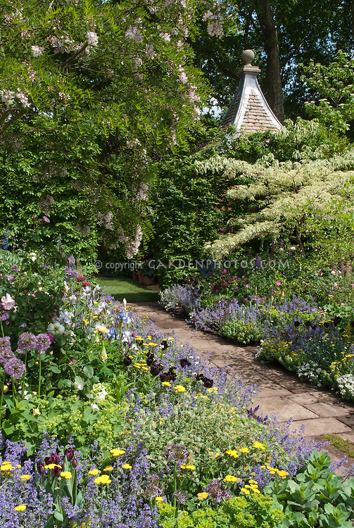 Garden stone path walkway through lush flowering garden with lots of different flowers, gazebo roof, wisteria vine