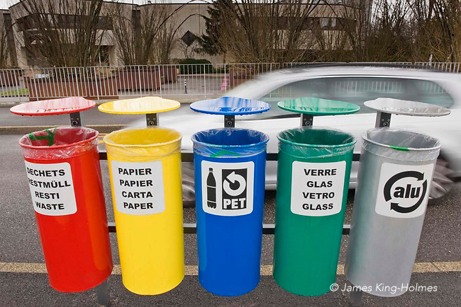 A bank of waste recycling bins for pedestrian use, seen in Geneva, Switzerland.  The bins are used for general waste, paper, plastic bottles, glass and aluminium.