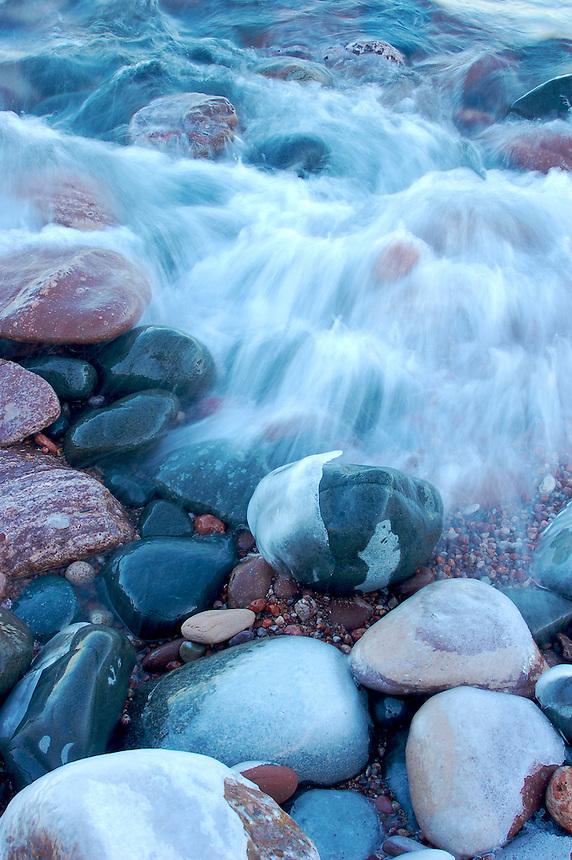 Waves on Lake Superior crashing over shoreline rocks.