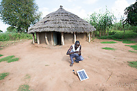 N. Uganda, Kitgum District. Young man generating light for his home with a solar panels.