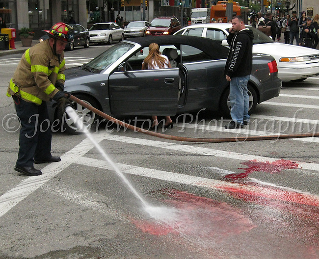 Pittsburgh firefighters use their hose to wash blood off the streets of Downtown after a Jimmy John's delivery man on a bicycle was struck by a grey Audi at the corner Wood Street and the Boulevard of the Allies.