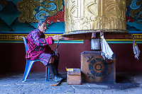 Punakha, Bhutan.  Old Man Turning Prayer Wheel at the Punakha Dzong.