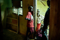 Eight year old Momoh (red t-shirt) stands in a doorway at the Interim Child Centre a children's home run by the St George Foundation. Currently 21 children live in the home, all there as a result of the ongoing ebola crisis. Momoh lost 22 family members to ebola, althou he survived the virus himeself. Beside him is nine year old Idris Conteh who's mother died from ebola and he is now one of the 3,500 orphans created by ebola.