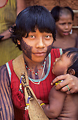 A - Ukre village, Xingu, Brazil. Young Kayapo Indian woman with her child; black face paint.