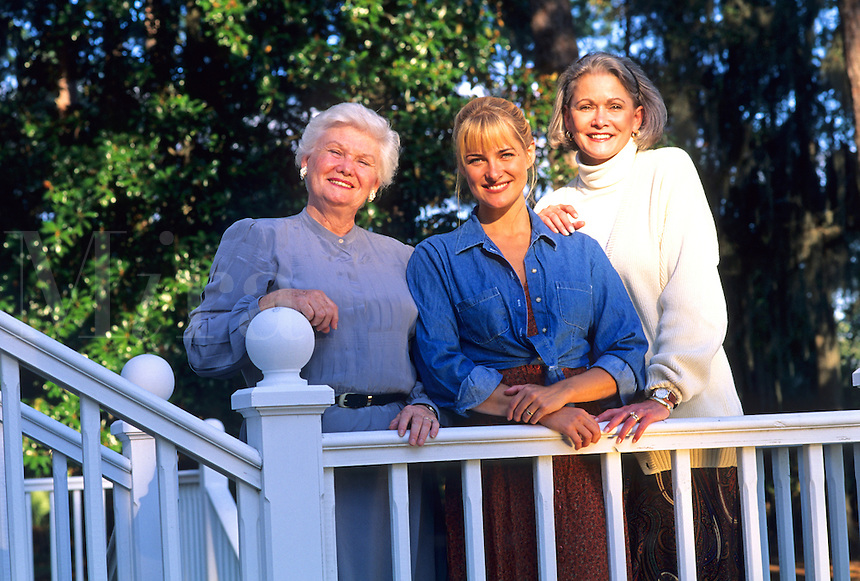Three generations of women pose for a portrait.