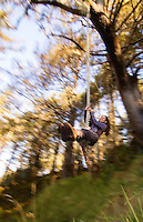 Young woman with eyes closed swinging on a rope swing with motion blur, Olympic National Park, Coastal Strip, WA.