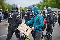 """Trotz Corona-Versammlungseinschraenkung gingen am 1. Mai 2020 in Berlin 3.000 Menschen in Berlin-Kreuzberg auf die Strasse. Sie protestierten u.a. fuer die Aufnahme von Gefluechteten aus den ueberfuellten griechischen Fluechtlingslagern und die Unterstuetzung von Automobilkonzernen wegen der Corona-Krise.<br /> Im Bild: Ein Mann mit einem Schild mit der Aufschrift """"Wir sitzen nicht im selben Boot! #LeaveNoOneBehind"""". Im Hintergrund eine Einheit Polizisten.<br /> 1.5.2020, Berlin<br /> Copyright: Christian-Ditsch.de<br /> [NUR FUER REDAKTIONELLE ZWECKE! Werbung nur auf Anfrage beim Fotografen. Inhaltsveraendernde Manipulation des Fotos nur nach ausdruecklicher Genehmigung des Fotografen. Vereinbarungen ueber Abtretung von Persoenlichkeitsrechten/Model Release der abgebildeten Person/Personen liegen nicht vor. NO MODEL RELEASE! Don't publish without copyright Christian-Ditsch.de, Veroeffentlichung nur mit Fotografennennung, sowie gegen Honorar, MwSt. und Beleg. Konto: I N G - D i B a, IBAN DE58500105175400192269, BIC INGDDEFFXXX, Kontakt: post@christian-ditsch.de<br /> Bei der Bearbeitung der Dateiinformationen darf die Urheberkennzeichnung in den EXIF- und  IPTC-Daten nicht entfernt werden, diese sind in digitalen Medien nach §95c UrhG rechtlich geschuetzt. Der Urhebervermerk wird gemaess §13 UrhG verlangt.]"""