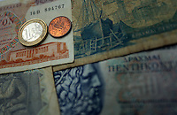 An o ld drachma coin and a one euro coin on old drachma paper notes<br />
