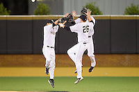 Luke Czajkowski (26), Grant Shambley (left) and Evan Stephens (rear) celebrate their win over the Maryland Terrapins at Wake Forest Baseball Park on April 4, 2014 in Winston-Salem, North Carolina.  The Demon Deacons defeated the Terrapins 6-4.  (Brian Westerholt/Four Seam Images)