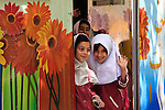 Iranian schoolgirls sneak away from the classroom for a chance to practice their English and smiles. On the streets of Shiraz, Iran in 2009.