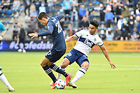 KANSAS CITY, KS - MAY 16: Michael Baldisimo #55 Vancouver Whitecaps with the ball tackled by Daniel Salloi #20 Sporting KC during a game between Vancouver Whitecaps and Sporting Kansas City at Children's Mercy Park on May 16, 2021 in Kansas City, Kansas.