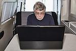 Senior man uses a laptop computer in a camper van.