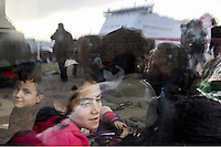 Pictured: Children on the bus that will take them to a nearby camp Friday 26 February 2016<br /> Re: Hundreds of refugees that crossed the border from Turkey to the Greek islands, have arrived at the port of Piraeus near Athens, Greece