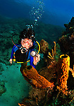 8 August 2010: SCUBA Diver Sally Herschorn holds a dive light to bring out the natural colors of coral and and sponges at Turtle Reef on Grand Cayman Island in the British West Indies. The Cayman Islands are renowned for their excellent scuba diving. Model Release on File. Mandatory Credit: Ed Wolfstein Photo