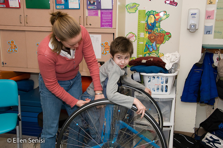 MR / Albany, NY.Langan School at Center for Disability Services .Ungraded private school which serves individuals with multiple disabilities.Teacher adjusts the straps on childs' Mobile Prone Stander. Boy: 10, Duchenne muscular dystrophy, expressive and receptive language delays.MR: Bud2; Ris4.© Ellen B. Senisi