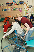 MR / Albany, NY.Langan School at Center for Disability Services .Ungraded private school which serves individuals with multiple disabilities.Teaching assistant helps position student in his Mobile Prone Stander. Boy: 10, Duchenne muscular dystrophy, expressive and receptive language delays.MR: Bud2 .© Ellen B. Senisi