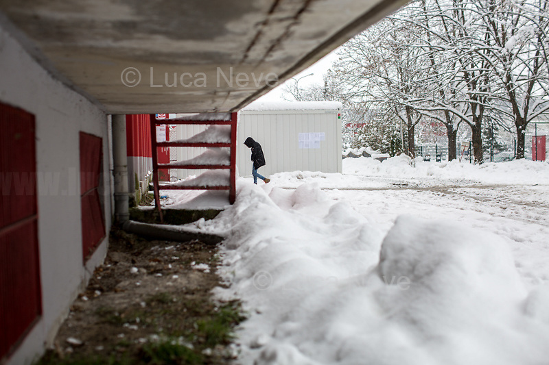 """Bihać, Bosanska Krajina, Bosnia, 15/12/2018.The Bira camp is a former fridge factory located outside Bihac. It is managed by the UN (ONU) agency called IOM (OIM) - International Organization for Migration. The camp is a huge hangar and it composed by tents and containers (mainly located in the area dedicated to most vulnerable people and families) 'donated' by the EU, Turkkizilayi, Crveni Kriz Grada Bihaca. The camp has got also a Health clinic, the """"Klinika"""", provided by DRC Danish Refugee Council and UNHCR and EU (UE). The People met outside the Klinica who showed their medical refers, their wounds and injuries claimed that they were beaten up by the Croatian Police which also allegedly stole their money and broke their smartphones after they were found trying to cross the border between Bosnia & Croatia, the beginning of the so called """"The Game"""" (1.). The very dangerous end of the """"Balkan route"""", the undetected border crossing throughout Croatia and then Slovenia, which people try numerous times to reach Italy or Austria. If they caught crossing any of the borders, they will be deported back to Bosnia, at """"square 1 of the Game"""".<br /> Clothes, food and a little bit of entertainment for the Children are provided by the Crveni Kriz Grada Bihaca, the Bosnian Red Cross, which also manages a sort of canteen.<br /> The IOM (OIM) provided data about the People living in the Bira camp while this reportage was made:<br /> -2067 people are the inhabitant of the camp (but obviously the number changes a lot and often)<br /> -187 unaccompanied minors all boys, mostly from Pakistan;<br /> -80 families: 325 family members, 145 children, 78 boys, 67 Girls.<br /> Moreover, the IOM (OIM) informed journalists that 550 People will go to the Borici camp when it's restructured and refurbished, mainly the most vulnerable people: families and unaccompanied minors.<br /> <br /> 1. http://bit.do/fgwYL"""