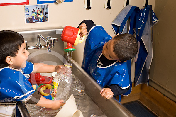 Education preschoool children ages 3-5 children playing at water table two boys playing together pouring water into bottle horizontal