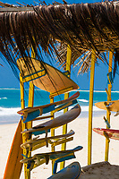 Surfboards under a thatched roof on the famous and beautiful Porto de Galinhas beach, with turquoise Atlantic Ocean background, in Pernambuco, Brazil
