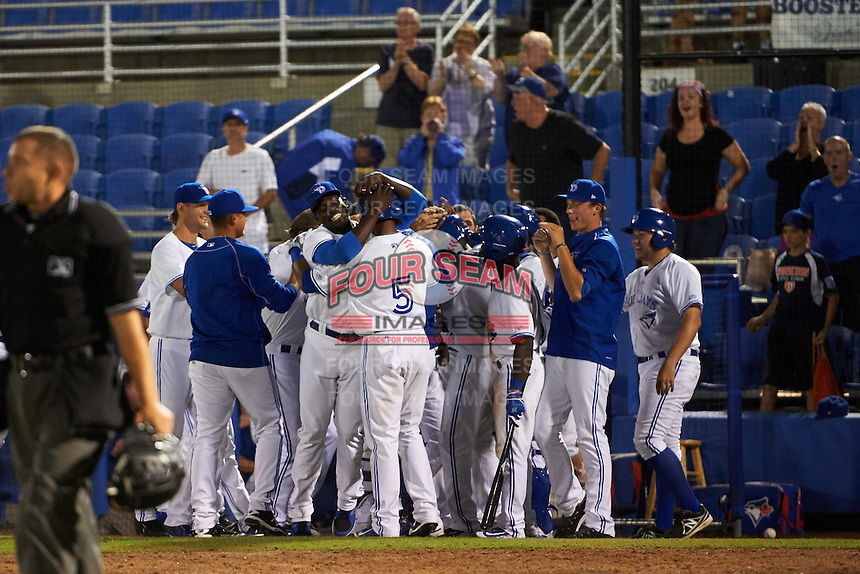 Dunedin Blue Jays Richard Urena (5) is hugged by Anthony Alford as teammates mob David Harris who scored the game winning run with Urena batting on a wild pitch during a game against the Palm Beach Cardinals on April 15, 2016 at Florida Auto Exchange Stadium in Dunedin, Florida.  Dunedin defeated Palm Beach 8-7.  (Mike Janes/Four Seam Images)
