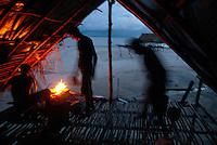Pescadores pernoitam após um dia de trabalho no litoral do Pará, na foz do rio Amazonas, em cabanas onde preparam sua alimentação e o local onde irão descansar a luz de lamparinas. Os pescadores chegam a capturar cerca de 200 quilos de pescado por dia entre: piramutabas, sardinhas, filhotes, pescada amarela, robalo e tainhas.<br /> Curuçá, Pará, Brasil.<br /> Foto: Paulo Santos<br /> 17/05/2009