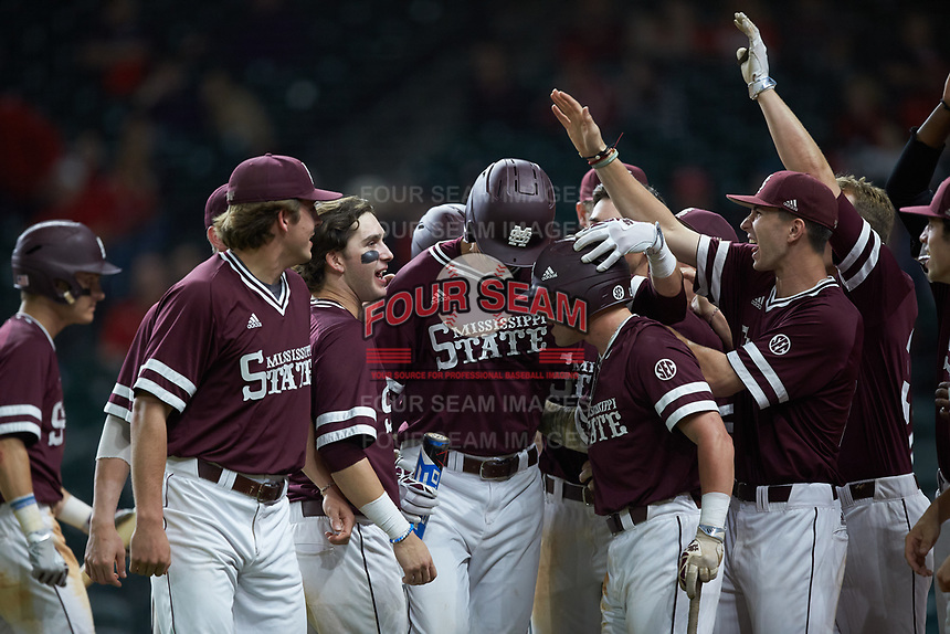 Tanner Poole (12) of the Mississippi State Bulldogs is greeted at home plate by his teammates after hitting a home run against the Louisiana Ragin' Cajuns in game three of the 2018 Shriners Hospitals for Children College Classic at Minute Maid Park on March 2, 2018 in Houston, Texas.  The Bulldogs defeated the Ragin' Cajuns 3-1.   (Brian Westerholt/Four Seam Images)