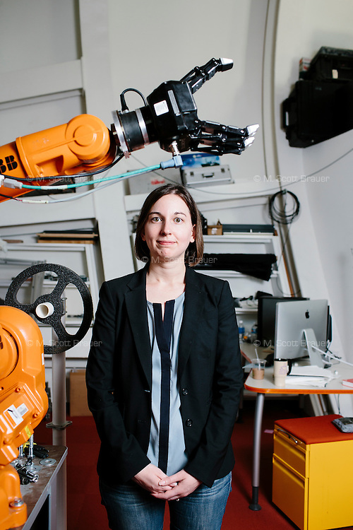 """Julie Shah is an Assistant Professor in the Department of Aeronautics and Astronautics and leads the Interactive Robotics Group in MIT's Computer Science and Artificial Intelligence Laboratory in Cambridge, Massachusetts, USA. She is seen here with an ABB industrial robot. Shah uses these robots in research on """"elbow to elbow"""" manufacturing, in which humans and robots work side by side in the same area."""