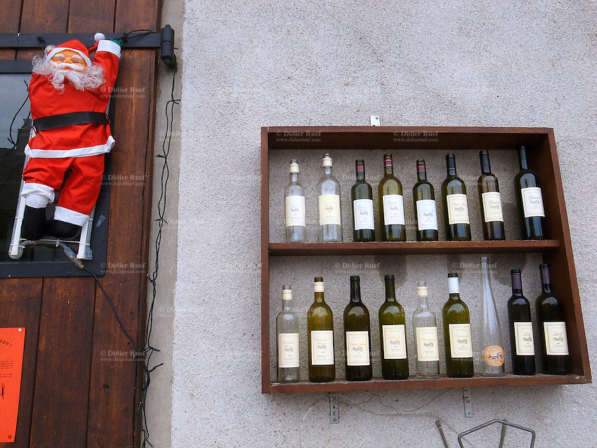 Switzerland. Canton of Geneva. Sézenove. On the wall of a wine grower, empty wine bottles on a shelf and a decoration of Father Christmas on an aluminium ladder. Sézenove is a small village distant 15 km from Geneva.  19.12.10 © 2010 Didier Ruef